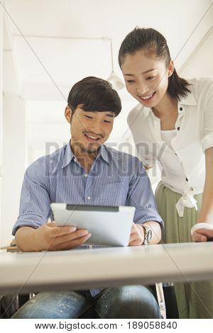 Chinese business people using tablet computer