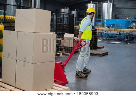 Factory worker pulling trolley of cardboard boxes in factory