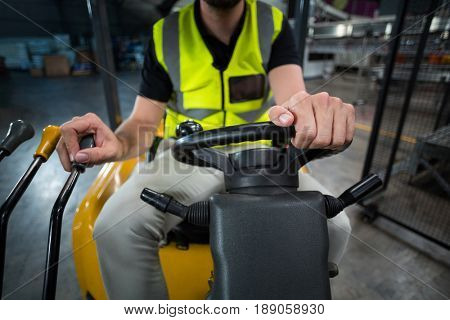 Mid-section of factory worker driving forklift in factory