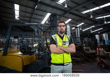 Portrait of factory worker standing with arms crossed in factory