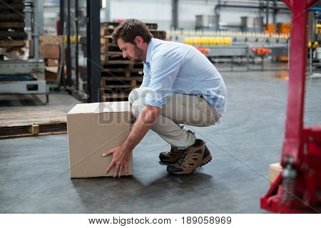 Attentive factory worker picking up cardboard boxes in factory