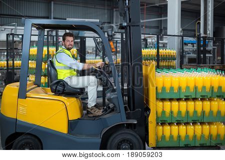 Portrait of factory worker loading packed juice bottles on forklift in factory