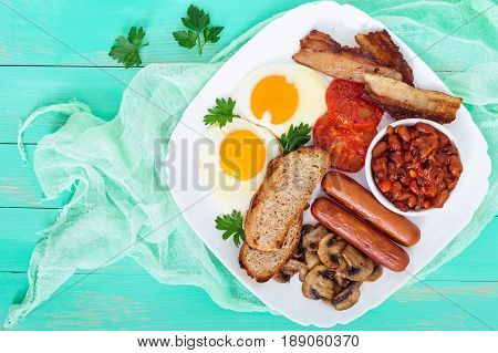 Traditional English breakfast: bacon mushrooms eggs tomatoes sausages beans toast on a white plate on a bright wooden background. Top view. England classic cuisine.