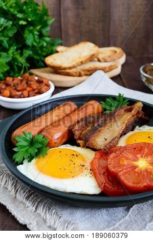 English breakfast: sausages bacon tomatoes egg beans in sauce fried mushrooms toast on a dark wooden background. Vertical view. Traditional classic food of England.
