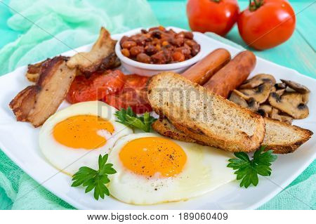 Traditional English breakfast: bacon mushrooms eggs tomatoes sausages beans toast on a white plate on a bright wooden background. England classic cuisine.