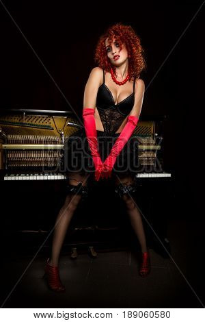 Sexy girl looks like a doll with curly redhead standing next to a piano, on a dark background. Fashion style.