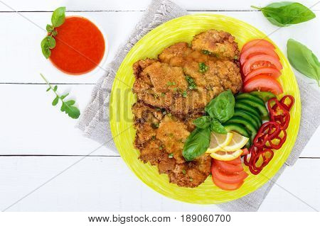 Schnitzel with vegetables tomato sauce on a white wooden background. Top view.