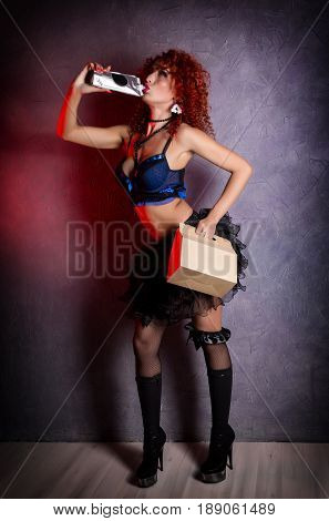 Curly redhead sexy girl looks like a doll holds a lunch box and drinks from a package, on a gray background. poppet for adult men