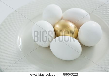 Close-up of golden Easter egg with white eggs in plate
