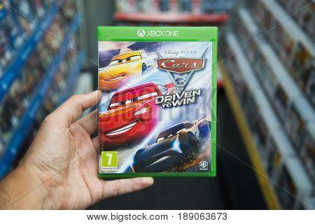 Bratislava, Slovakia, circa april 2017: Man holding Cars 3 Driven to Win videogame on Microsoft XBOX One console in store