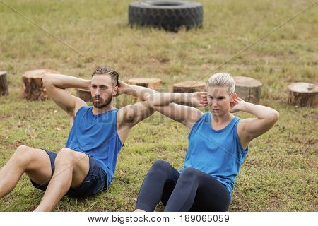 Fit people performing crunches exercise in boot camp