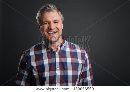 Good laugh. Radiant bright nice guy looking enthusiastic while laughing and standing isolated on grey background