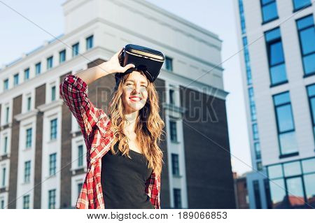 Beautiful young woman with long hair wearing virtual reality headset in an urban context.