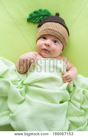 Baby with a knitted hat on back. Newborn child boy lying on a bed in the cap