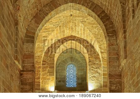 Plain stone walls and arches and an Arabic-style window in the Royal Chapel (Cappella Palatina) of the Norman Palace (Palazzo dei Normanni) - Palermo Sicily Italy