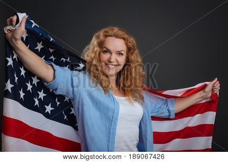 Glorious country. Stunning graceful confident lady making a photoshoot and posing with national flag while standing isolated on grey background