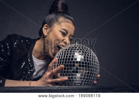 Glamour Asian Girl Biting Disco Ball Isolated On Grey
