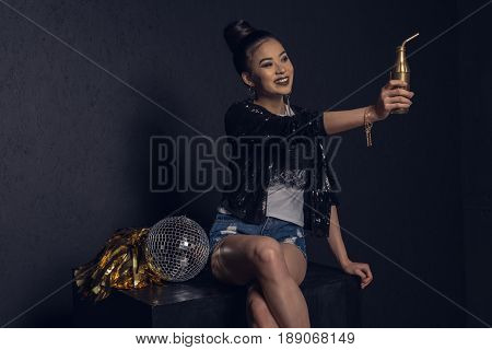 Glamour Asian Disco Girl With Golden Bottle, Disco Ball And Pom-pom Smiling