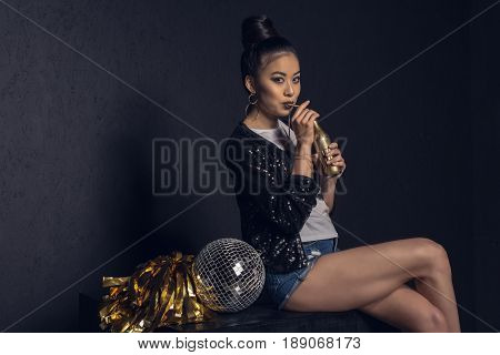 Glamour Asian Disco Girl With Golden Bottle, Disco Ball And Pom-pom Posing And Looking At Camera