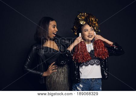 Beautiful Smiling Young Women Having Fun With Shiny Pom-poms Isolated On Black