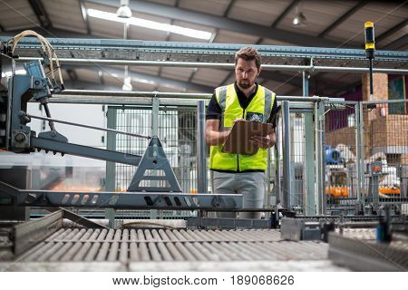 Attentive factory worker maintaining record on clipboard in factory