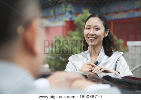 Chinese businesswoman standing by car