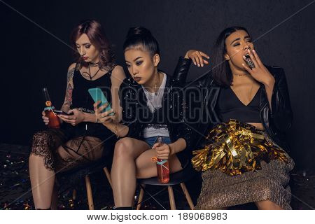 Women Using Smartphones With Bored Friend Near By At Party