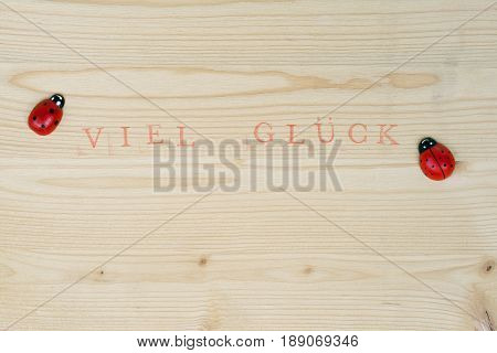 Stamped text Good luck on wood and ladybug, background