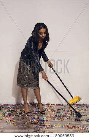 Young African American Girl Tidying Up Confetti With Dust Tray And Broom