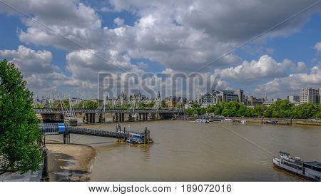 London River Thames view looking towards Hungerford railway bridge. Shows vessels and Festival Pier.
