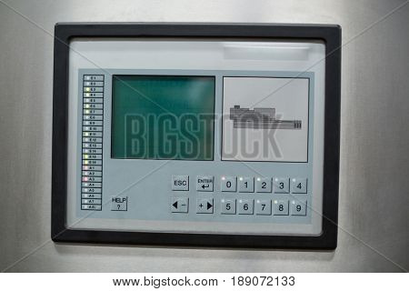 Close-up of control button and screen on factory machine