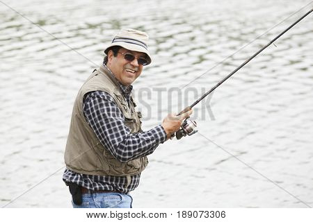 Smiling Hispanic man fishing in lake