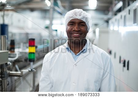 Portrait of smiling factory engineer standing in bottle factory