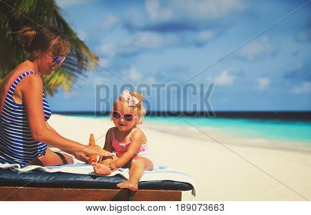 sun protection -mother applying sunblock cream on daughter shoulder on beach
