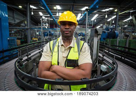 Confident factory worker standing near the conveyor belt in factory