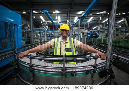 Smiling factory worker standing near the conveyor belt in factory