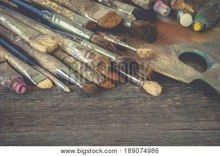 Brushes of the artist tubes with oil paint and a palette lie on the old easel