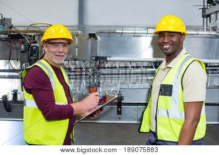 Portrait of two factory workers with clipboard standing next to production line in drinks production plant