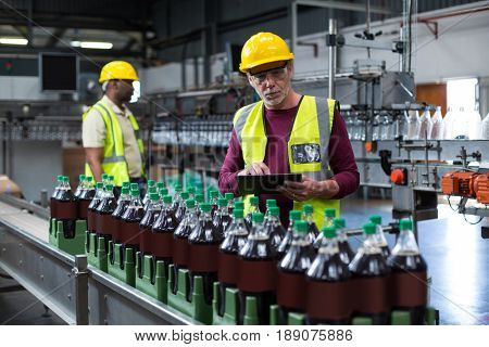 Factory worker with digital tablet monitoring drinks production line at factory