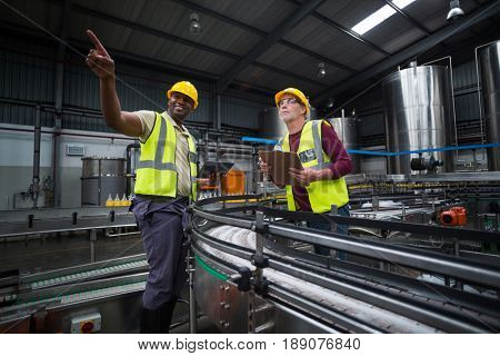 Two factory workers looking up in drinks production plant