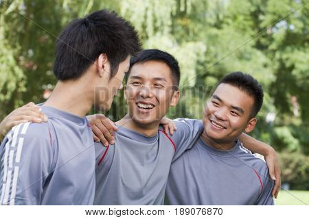 Chinese soccer players talking in park