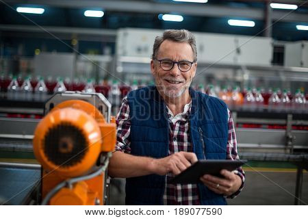Portrait of smiling factory worker standing with a digital tablet in drinks production plant