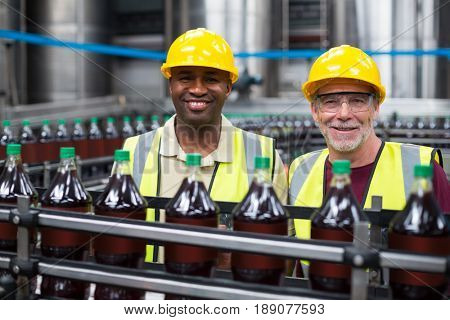 Smiling factory workers monitoring drinks production line in the factory