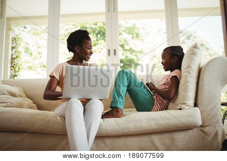 Mother and daughter using laptop and digital tablet at home
