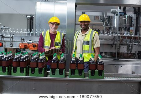 Portrait of two factory workers monitoring cold drink bottles at drinks production plant