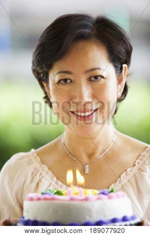 Older Asian woman holding birthday cake