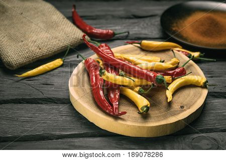 Red and yellow chili pepper of black wooden table. Black plate with powdered pepper. Bagging at the background.