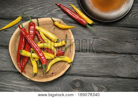 Red and yellow chili pepper of black wooden table. Black plate with powdered pepper. Overhead view at chili pepper on a wooden table.