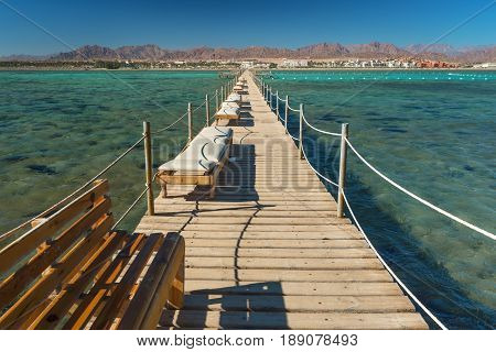 Pier with chaise longues in the sea in resort. Summer vacation. View at a clear sea with turquoise water. Summer vacation at a sea coastline in a exotic country.