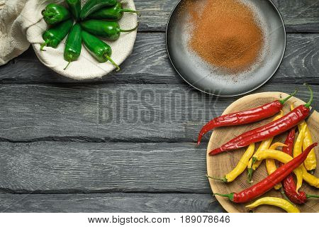 Red yellow and green chili pepper of black wooden table. Black plate with powdered pepper. Overhead view at chili pepper on a wooden table. Green pepper in the bagging